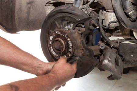 Photo pour Mécanique des mains réparé les freins sur une voiture particulière - image libre de droit