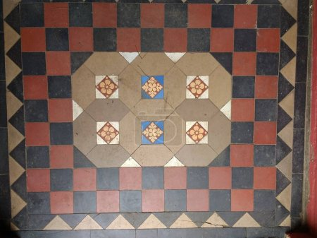 Photo pour Carrelage intérieur en mosaïque dans un design décoratif en céramique victorienne, les briques réutilisées récupérées en brun bleu blanc et rouge posées dans un motif géométrique carrelage vintage antique dans le couloir vue à plat - image libre de droit