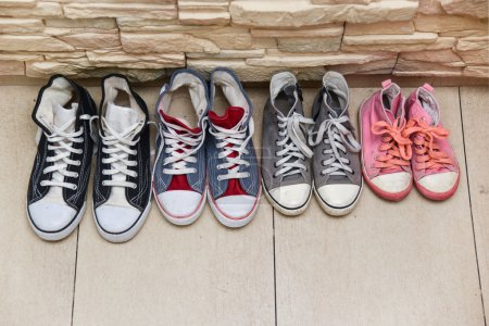 Photo for Sport shoes of the four people family in a row - Royalty Free Image