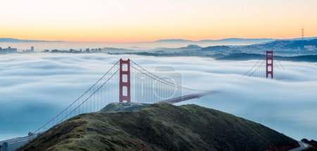 Photo for Sun rising on a Golden Gate Bridge with low lying fog running through the tower cables. Great for magazines, bloggers, backgrounds. - Royalty Free Image