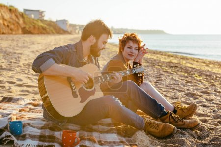 Photo pour Jeune couple caucasien jouer de la guitare sur la plage au coucher du soleil - image libre de droit