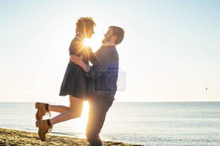 Photo pour Heureux couple aimant s'amuser sur la plage au coucher du soleil - image libre de droit
