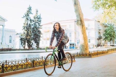 Photo pour Vélo à pignon fixe jeune brunette dans la ville par une journée ensoleillée - image libre de droit
