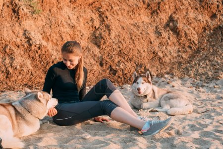 Woman and husky at the beach