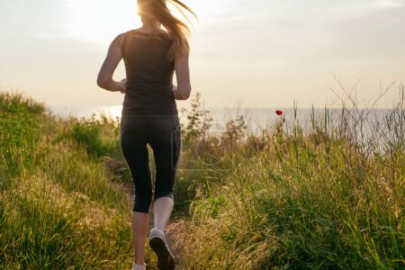 Photo for Running woman. Female runner jogging during the sunrise on beach. - Royalty Free Image