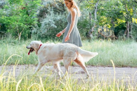 girl walking with dog in park