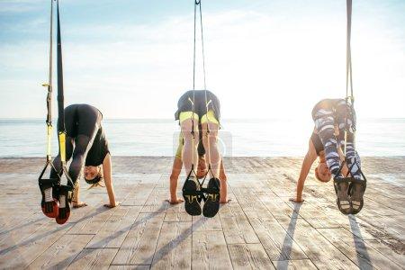 Group of people having Trx training