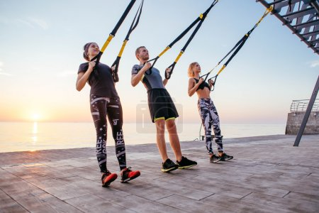 Group of people having Trx training