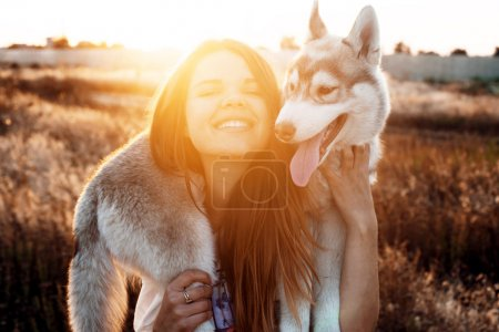 Young caucasian female playing with her siberian husky puppy in the field during the sunset. Happy smiling girl having fun with puppy outdoors in beautiful light