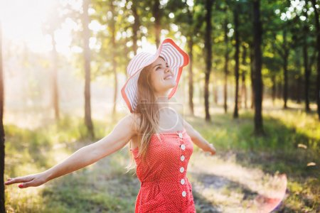 young beautiful caucasian female in hat enjoying the sun in park