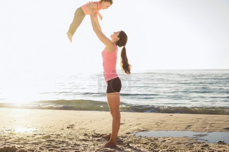 family workout - mother and daughter doing exercises on beach.