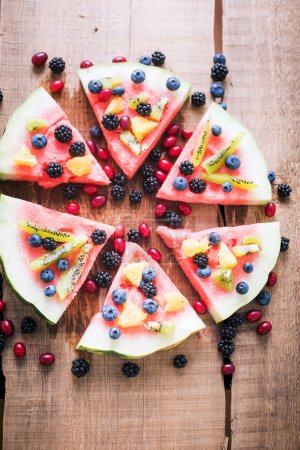 colorful tropical fruit watermelon pizza topped with kiwifruit,