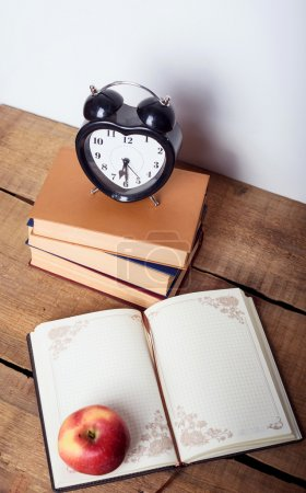 books, alarm clock, notepad, apple  on wooden background. Education equipment, education concept