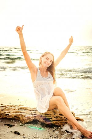 young beautiful caucasian female enjoying the sun on beach during sunrise or sunset