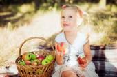 Bambina con le mele nel parco