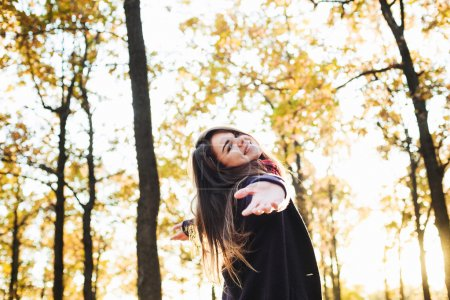 Photo for Young happy woman with cheering hands in park. Female enjoying autumn sun - Royalty Free Image