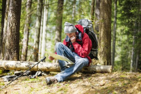 young caucasian male with a map in the forest, hiker looking at map outdoors