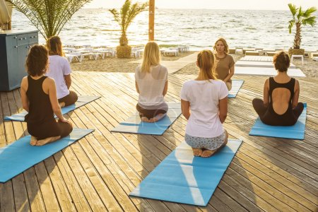 group of young females practicing yoga on the seaside during the sunrise