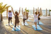 Skupina mladých žen, cvičení jógy u moře během východu slunce