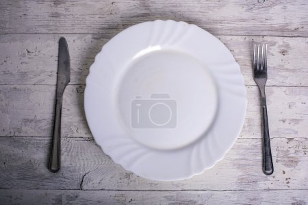 Photo for Plate, knife and fork on white vintage wooden background - Royalty Free Image