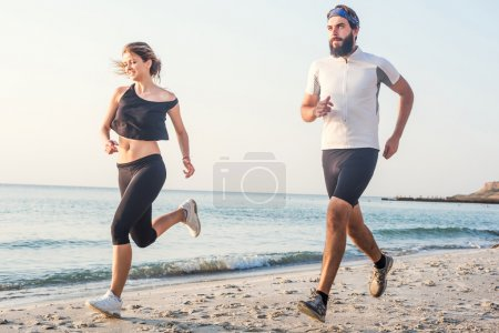 Photo for Running people - woman and man athlete runners jogging on beach. Fit young fitness couple exercising healthy lifestyle outdoors during sunrise or sunset - Royalty Free Image