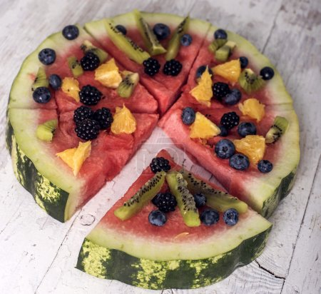 Colorful tropical fruit watermelon pizza topped with kiwifruit, blueberries, orange and fresh berries cut into segments on a rustic wooden board