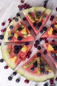 Barevné tropické ovoce meloun pizzu s kiwi, borůvky, oranžové a čerstvé jahody nakrájíme na segmenty na rustikální dřevěné desce