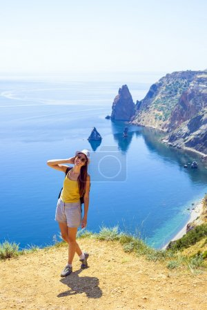 young caucasian female hiking on a cliff above the sea