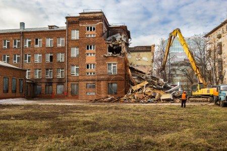 Photo pour Excavatrice démolit l'ancien bâtiment de l'école soviétique à Moscou - image libre de droit