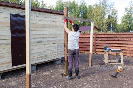 Photo pour Homme de mesure un poteau en bois au niveau - image libre de droit
