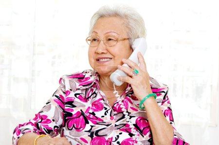 Photo pour Gai asiatique senior femme parler sur l 'téléphone - image libre de droit