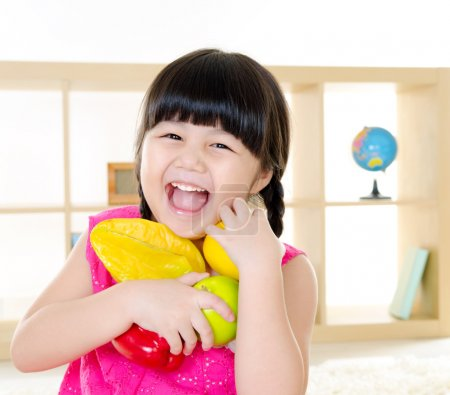 Photo for Cheerful asian girl holding fruits - Royalty Free Image