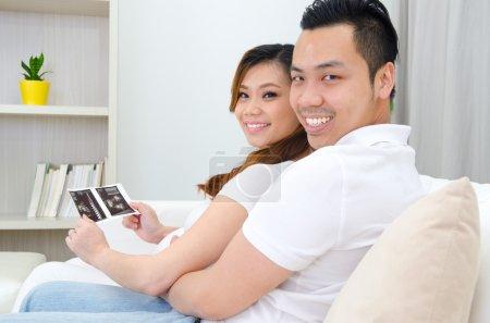 Photo pour Couple asiatique regardant l'échographie de leur bébé à naître - image libre de droit