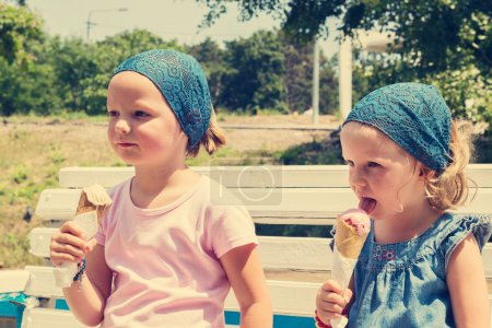 Little cute girls (sisters) eat ice cream. Selective focus.