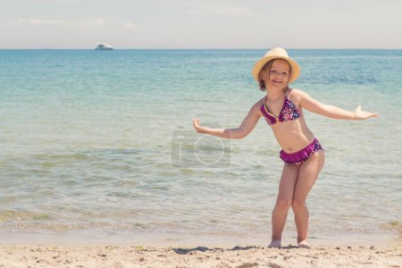Funny little girl playing on the beach.