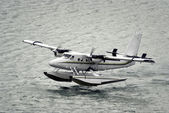 Twin propeller engine hydroplan taking off from water surface