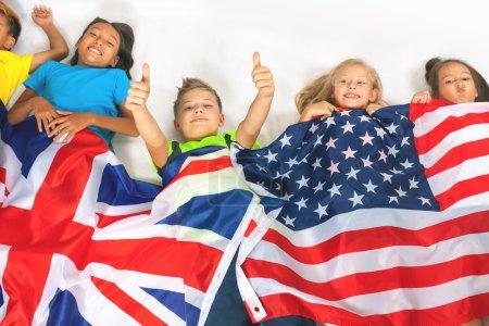 Photo pour Funny kids tenant le drapeau de la Grande-Bretagne et le drapeau national américain. Groupe d'écoliers. Étudiants multiethniques. Retour à l'école. Amis. Ventilateurs, Rio. Fond blanc - image libre de droit