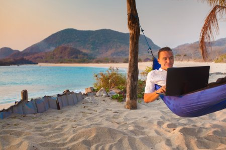 Man uses laptop remotely at the beach...
