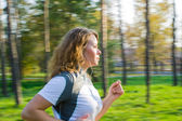 Young attractive woman running in forest