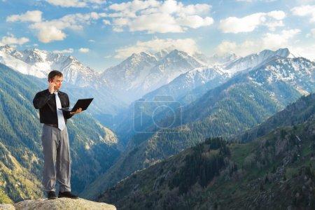 Photo pour Image d'un homme d'affaires debout sur le sommet de la montagne, à l'aide d'un ordinateur portable, parle au téléphone. En arrière-plan un beau panorama de la vallée avec de hauts sommets . - image libre de droit