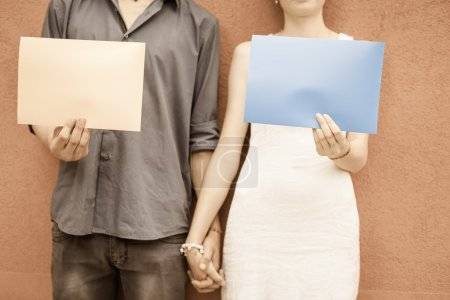 Closeup couple holding hands and holding frames at wall background