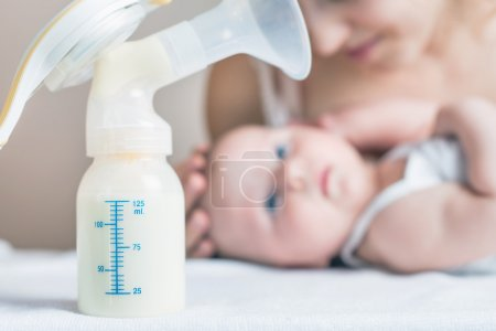 Manual breast pump and milk at background