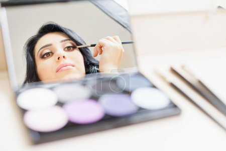 makeup artist woman doing make-up using cosmetic brush for yourself