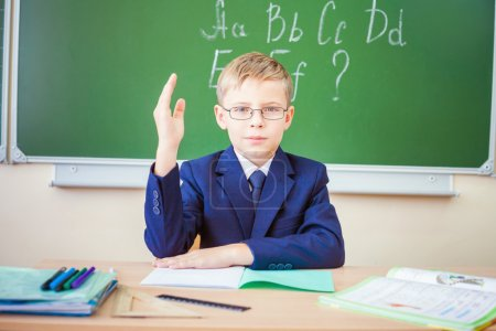 Schoolboy ready to answer and raised hand up