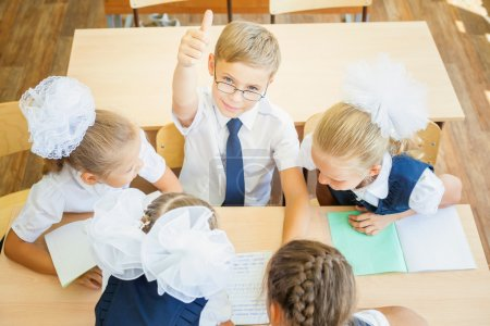 Group of schoolchildren at school classroom sitting at desk