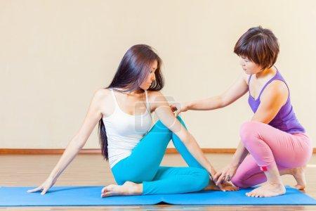 Photo pour Entraîneur asiatique conduit des cours de yoga de groupe à l'intérieur, au cours de yoga. Concept d'un mode de vie sain et de la bonne attitude envers la vie - image libre de droit