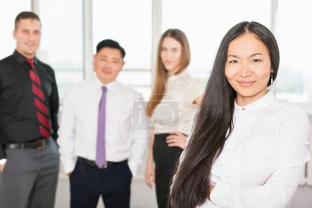 Photo pour Successful asian business woman with magnificent long hair and there is business team at background. Image symbolizes a successful corporation or company - image libre de droit