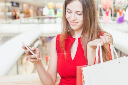 Fashion beautiful woman with bag using mobile phone, shopping center