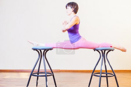Asian woman stretching for yoga exercise at home by chairs