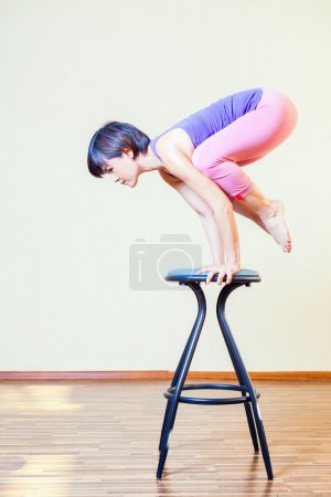 Asian woman doing exercise or yoga at home at chair